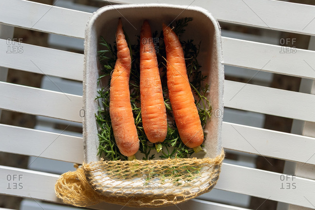 From above of clean ripe carrots placed in paper container on wooden table