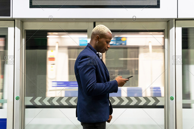 Side view of serious African American businessman standing in subway train and messaging on smartphone while commuting to work