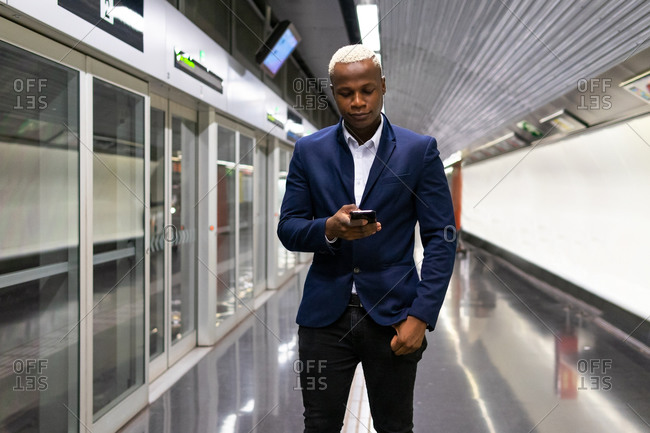 African American businessman standing in subway train and messaging on smartphone while commuting to work