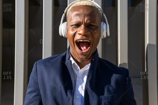 Dreamy African American male entrepreneur in suit standing in city and enjoying songs in wireless headphones