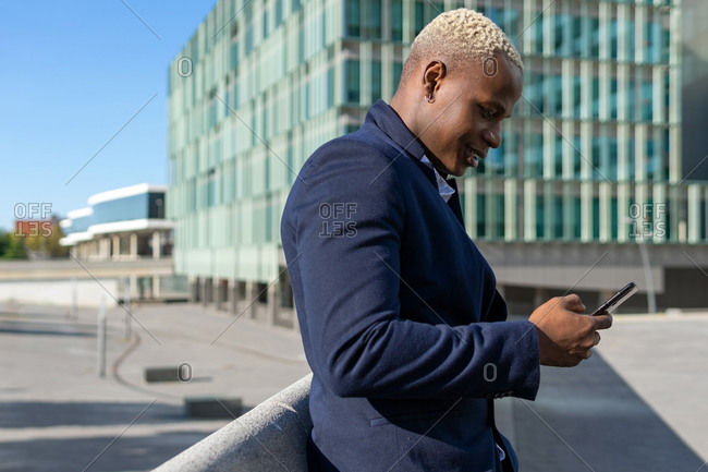 Side view of smiling African American businessman standing in downtown and messaging on smartphone while discussing project details online