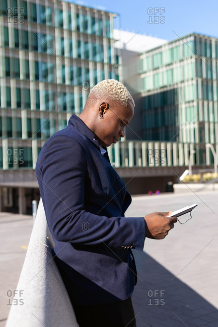 Side view of smiling African American businessman standing in downtown and browsing tablet online