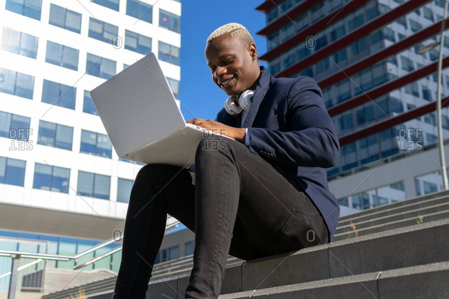 From below of content African American male entrepreneur in stylish wear sitting on stairs in city center and typing on laptop while working remotely on project