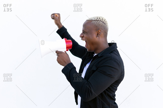 Side view of cheerful African American male shouting in loudspeaker while standing with fist up on white background