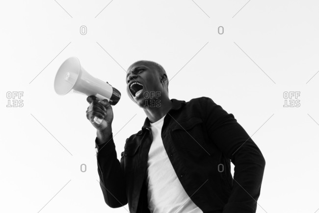 From below of cheerful African American male shouting in loudspeaker while standing on white background