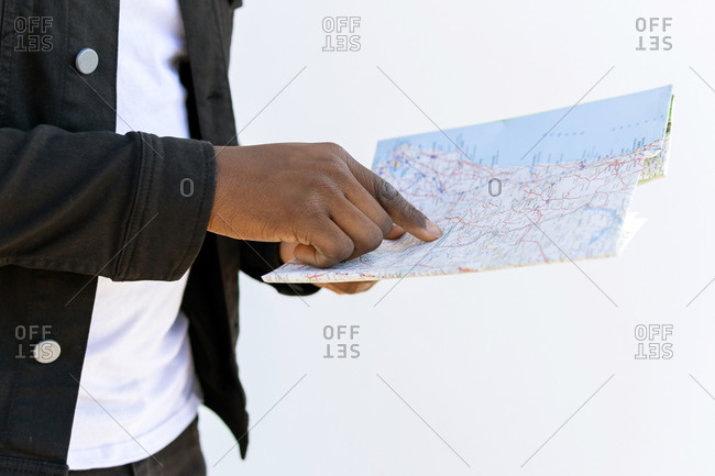 Side view of crop anonymous ethnic male tourist orientating with paper map in city during trip