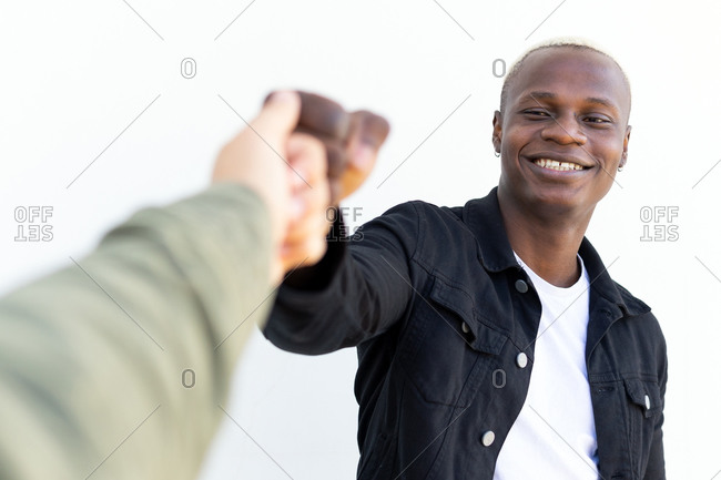 Delighted diverse male friends greeting each other and bumping fists while standing in city