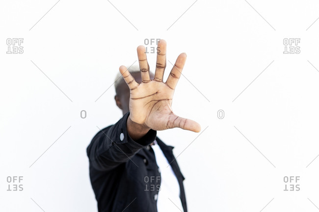 Anonymous African American male in casual outfit reaching hand toward camera and covering face while standing on street and showing stop gesture