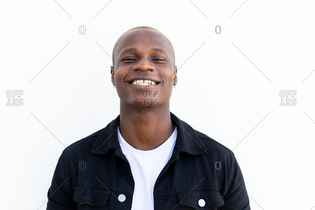 Satisfied African American male in casual outfit smiling and looking at camera on white background