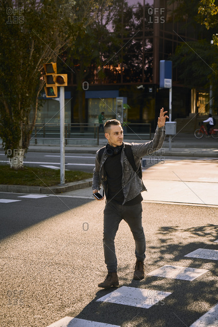 Young male crossing road in city and waving hand while looking away and catching taxi