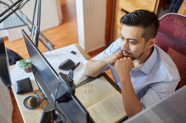 High angle side view of young male student sitting at table and working on computer monitor while preparing for exam in university