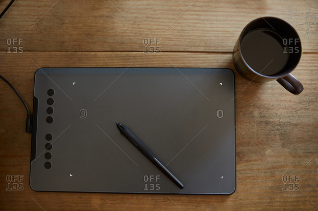 Top view of arrangement of modern graphics tablet with stylus and cup coffee on wooden table