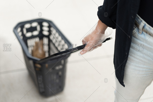 From above of crop unrecognizable female buyer in cellophane gloves carrying shopping basket while doing purchases in supermarket during coronavirus pandemic