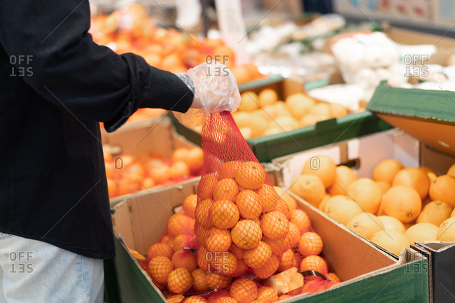 Side view of crop anonymous customer in cellophane gloves picking sack with fresh tangerines while visiting supermarket during coronavirus pandemic