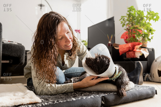 Smiling female owner caressing cute dog in Elizabethan collar while lying on bed on floor in cozy room and looking at each other