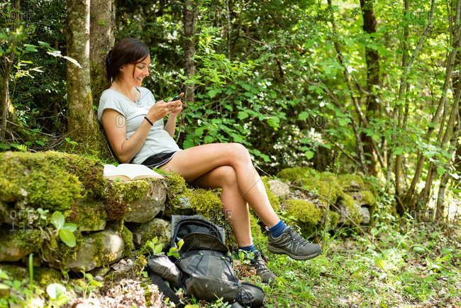 Side view of delighted female traveler relaxing on mossy stones in green woods and browsing cellphone during summer adventure