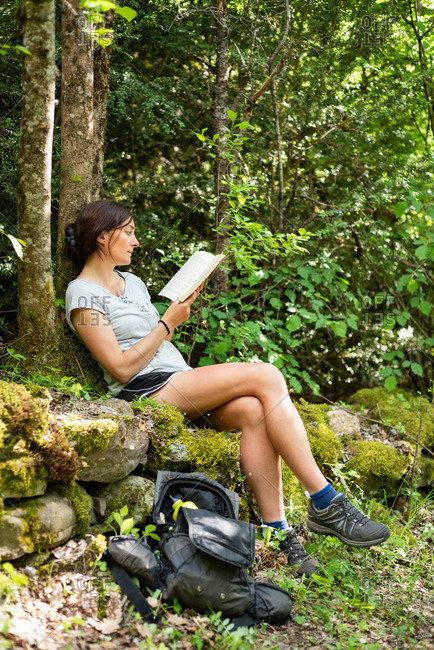 Side view of focused female sitting on mossy stones in woods and enjoying interesting story in book while spending time in nature