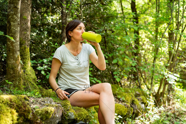 Female explorer resting on mossy stones in forest and drinking fresh water from bottle while having break during trekking in summer