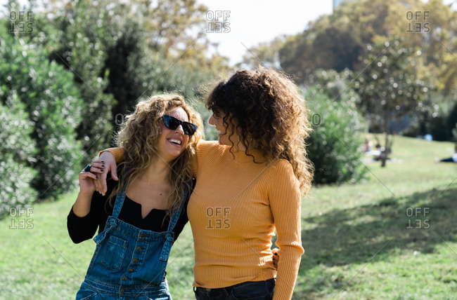 Young caucasian female friends smiling and cuddling in park while looking at each other
