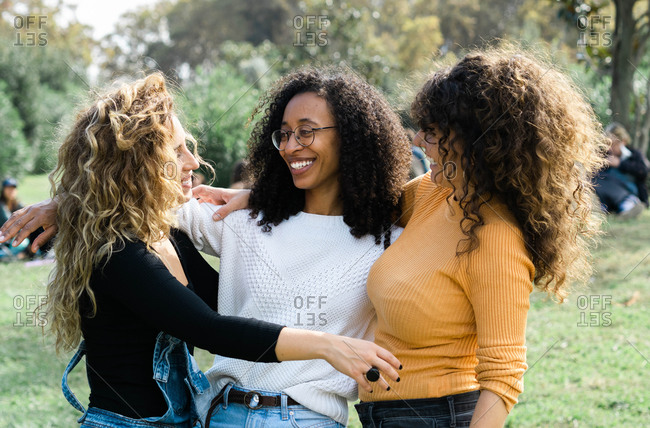 Group of young multiracial female friends smiling and cuddling in park while looking at each other