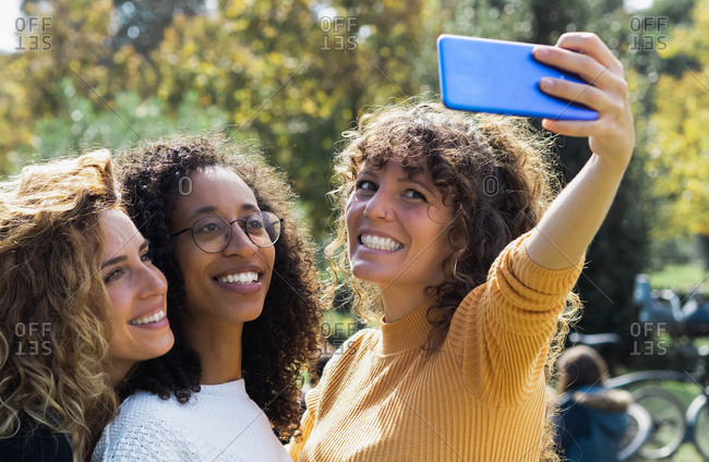 Group of delighted multiracial females with curly hair taking selfie on smartphone while enjoying sunny day at weekend in park