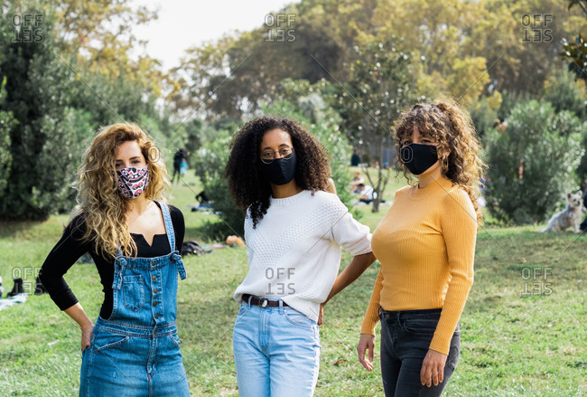 Group of multiracial women wearing protective masks standing in park during coronavirus pandemic and looking at camera