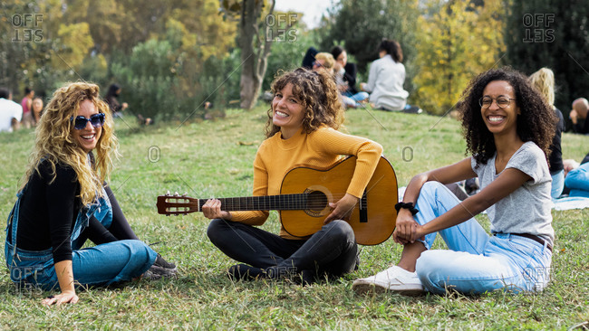 Group of cheerful multiracial female friends sitting on meadow in park and playing acoustic guitar while spending weekend together and looking at camera