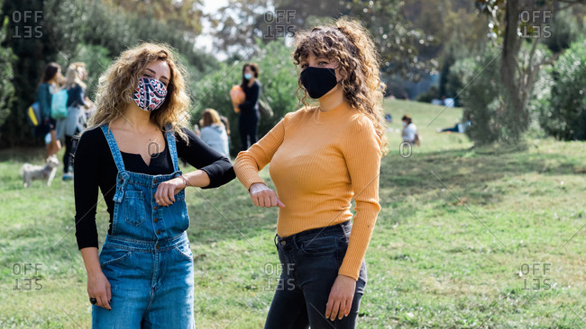 Female friends wearing protective masks bumping elbows while greeting each other during coronavirus epidemic
