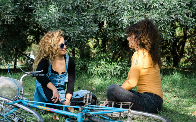 Friendly women sitting on green lawn and giving while looking at each other and relaxing in park near bike