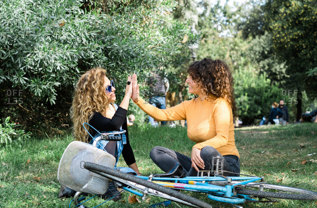 Friendly women sitting on green lawn and giving high five while looking at each other and relaxing in park