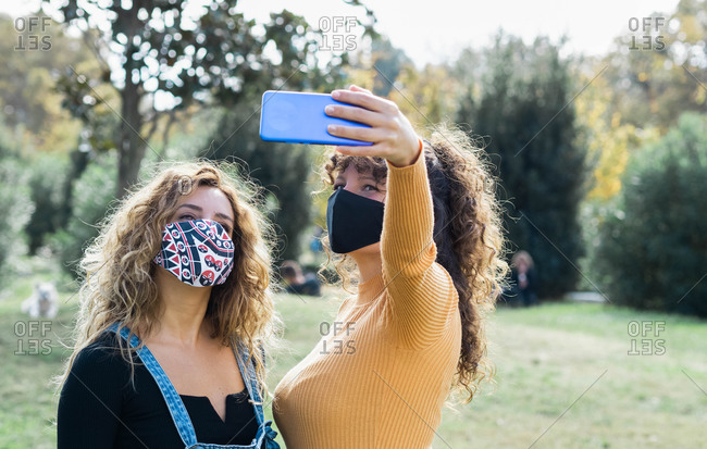 Delighted friendly women cuddling and taking self portrait on smartphone while wearing masks during coronavirus epidemic