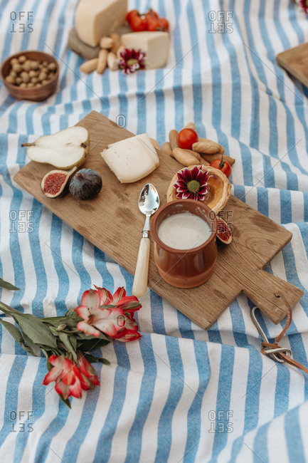 From above delicious cocoa drink and sweet tartlet placed on wooden cutting board on blanket in park for picnic