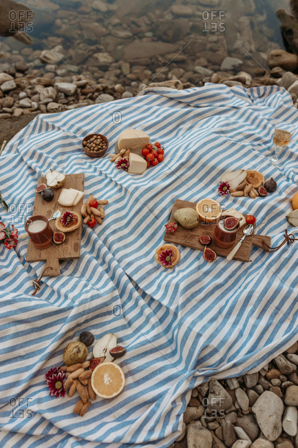 High angle of appetizing assorted food on wooden cutting board arranged on blanket placed near river for picnic