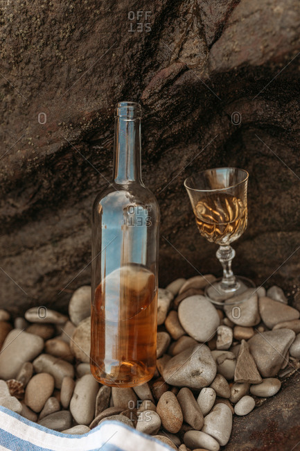 Crystal bottle of alcohol beverage and glass placed on stones on beach near rock for picnic