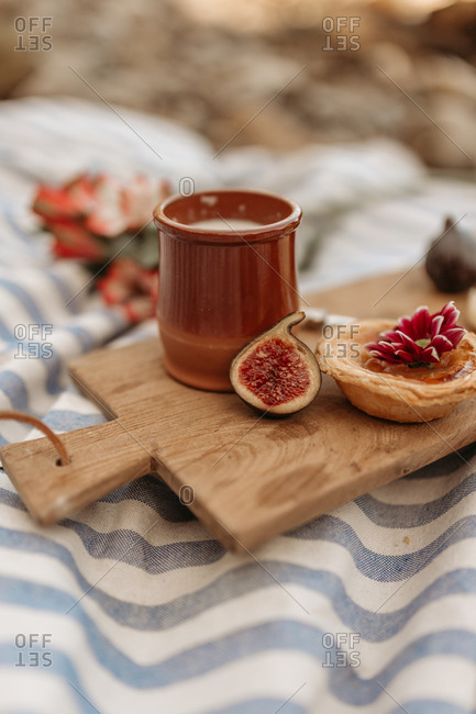 Delicious cocoa drink and sweet tartlet placed on wooden cutting board on blanket in park for picnic