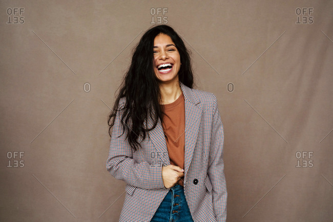 Delighted ethnic female in casual jacket laughing with closed eyes on brown background in studio