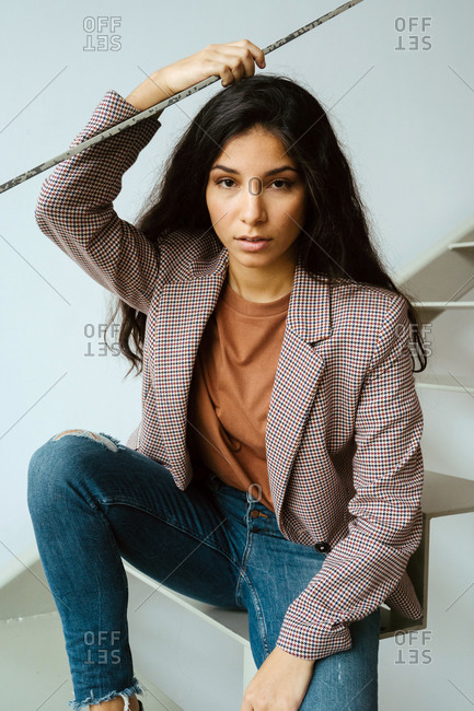 Young charming ethnic female in smart casual style sitting on staircase and looking at camera