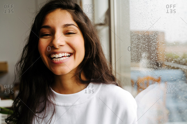 Young cheerful ethnic female standing near window with raindrops and looking at camera