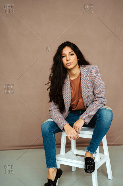 Stylish ethnic female model in trendy smart casual outfit sitting on chair and looking confidently at camera