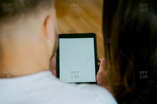 Back view high angle of couple browsing tablet with empty screen while entertaining at weekend