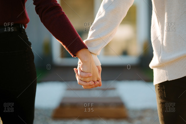 Crop anonymous couple tenderly holding hands while standing on blurred background of house on sunny day