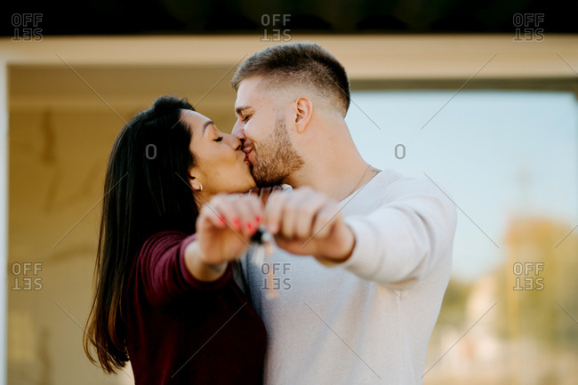 Young couple with keys kissing and showing keys to camera on background of new house