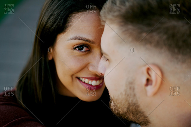 Close up of cheerful woman looking at camera while bonding face to face with her boyfriend