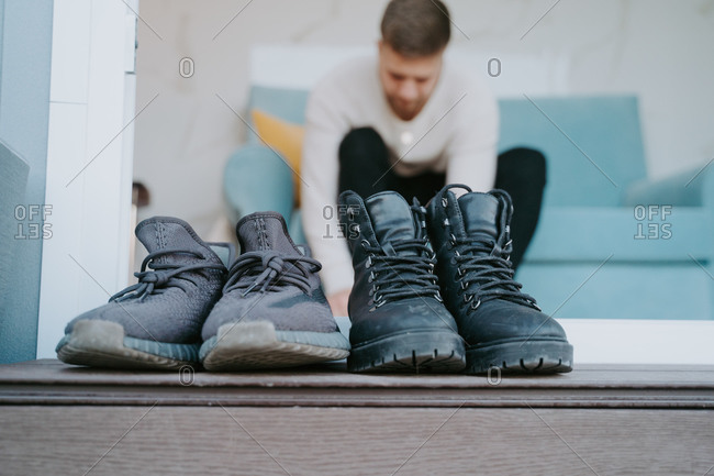 Ground level of dirty boots and sneakers placed at doorway of modern house of background of blurred man sitting on sofa