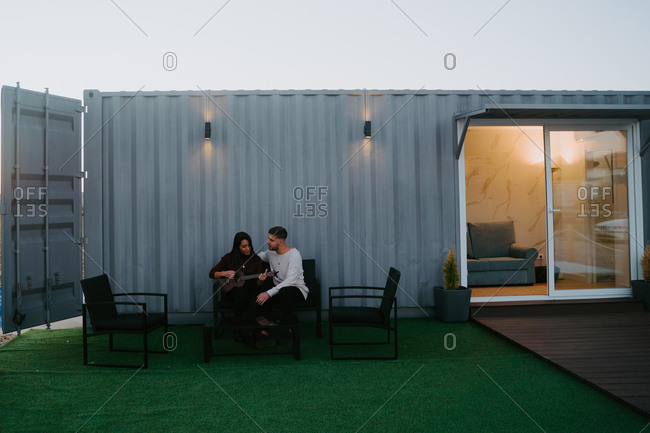 Tranquil couple sitting on backyard of container house and playing ukulele while enjoying music in evening