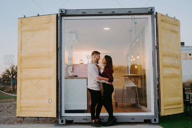 Side view of smiling couple cuddling near window of modern container house at sunset in countryside
