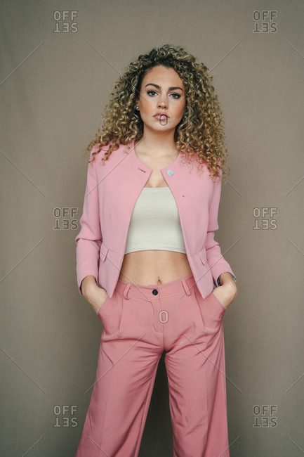 Young female with curly hair and in trendy apparel posing in studio and looking at camera