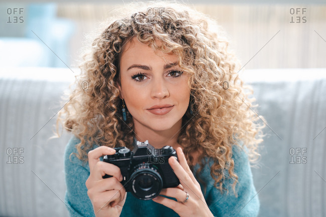 Charming female with curly hair taking picture on photo camera in bright apartment