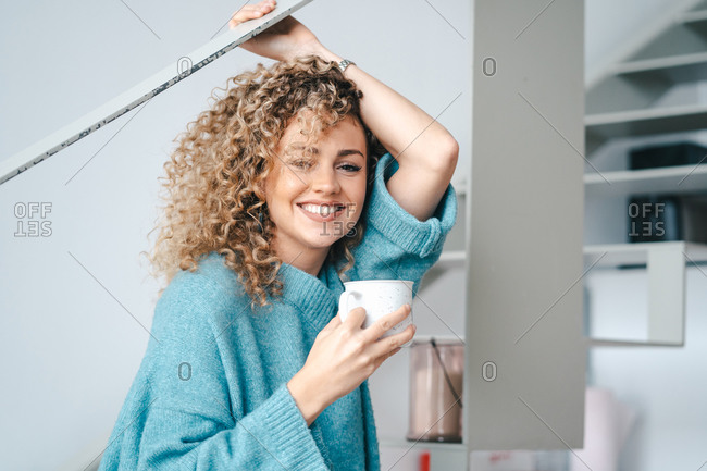 Side view of smiling female in oversize warm sweater sitting on staircase with a cup of coffee in apartment and looking at camera