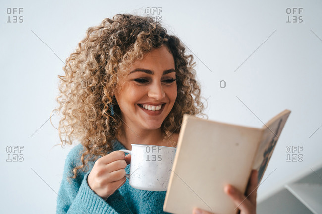 Cheerful female in cozy domestic sweater leaning on stairs at home while enjoying interesting story and drinking hot coffee at weekend